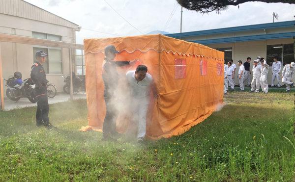 煙体験ハウスの煙の中から苦しそうに出てくる社員